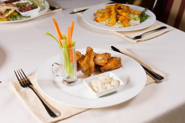 手羽先と野菜とレストランのテーブルのプレートのディップ