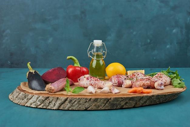 Ali di pollo su una tavola di legno con verdure.