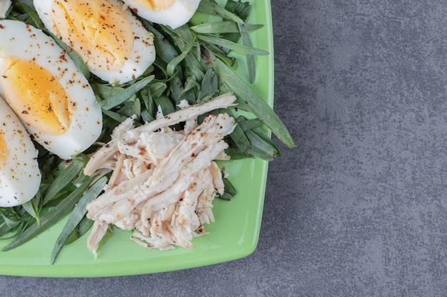 녹색 접시에 삶은 계란과 닭고기입니다.