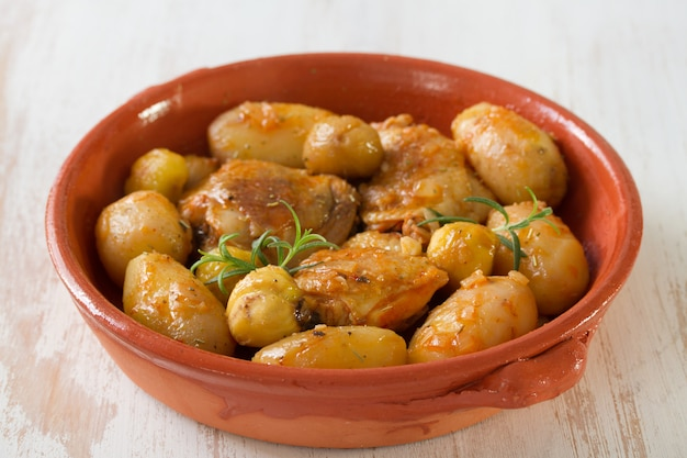 Chicken with potato and chestnuts on ceramic dish