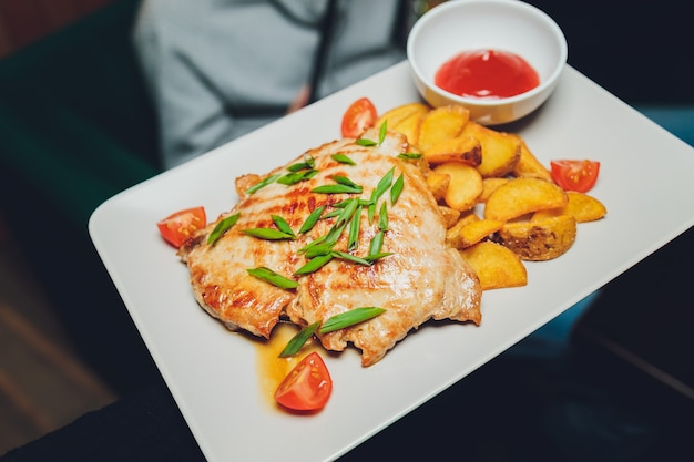 Chicken with roasted potatoes on a white plate.