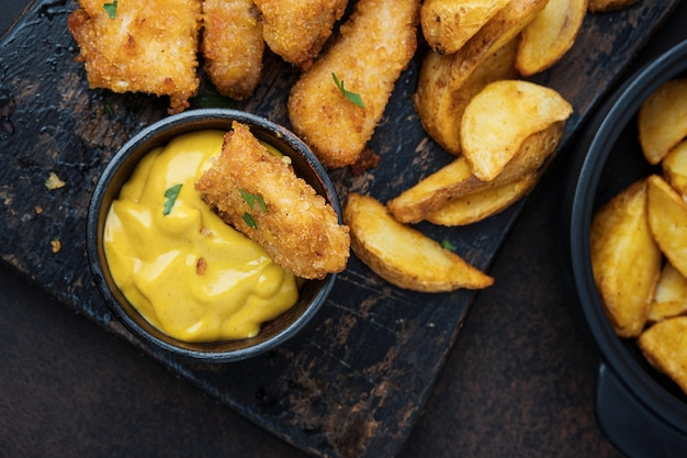 Курица с соусом и картофелем на темной столешнице