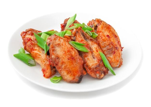 데리야끼 소스와 파를 곁들인 치킨. 하얀 접시에. 흰색 배경에. 외딴.