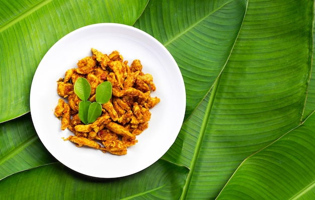 Курица с желтой пастой карри на банановых листьях. тайская еда