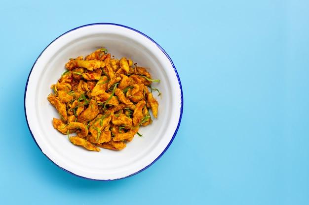 Цыпленок с желтой пастой карри на синем фоне. пряная тайская еда