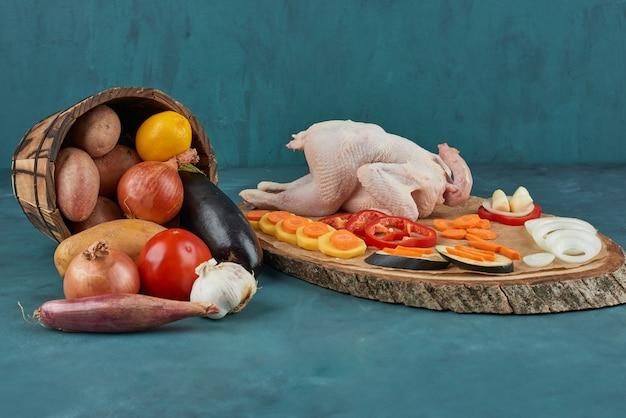 Pollo su una tavola di legno con verdure nel secchio.