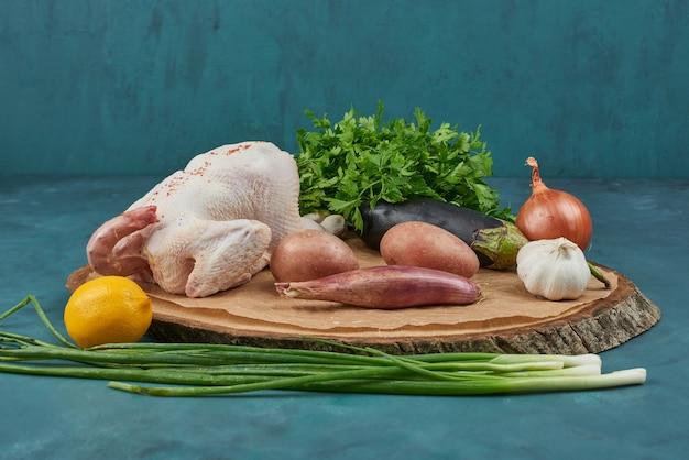 Pollo su una tavola di legno con verdure.