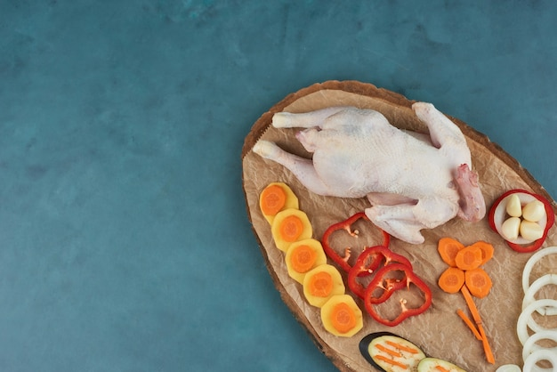 Chicken on a wooden platter with vegetables.