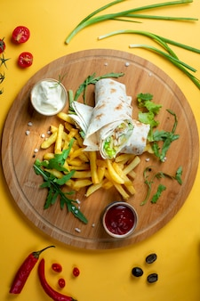 Chicken wrap with side fries and herbs