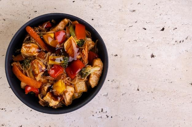 검은 세라믹 그릇에 담긴 치킨 야키소바 - 위쪽 전망.