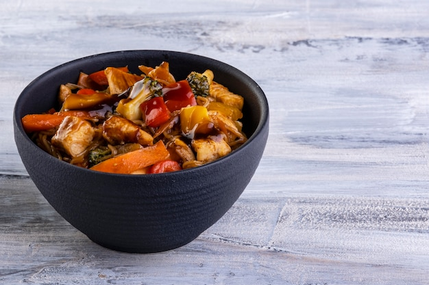 블랙 세라믹 그릇에 담긴 치킨 야키소바.