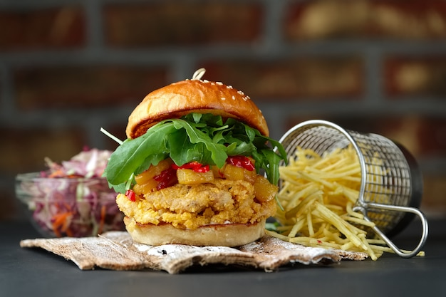 Chickenburger on the wooden plates with cheese, bacon, tomatos, green and red salad and french fries