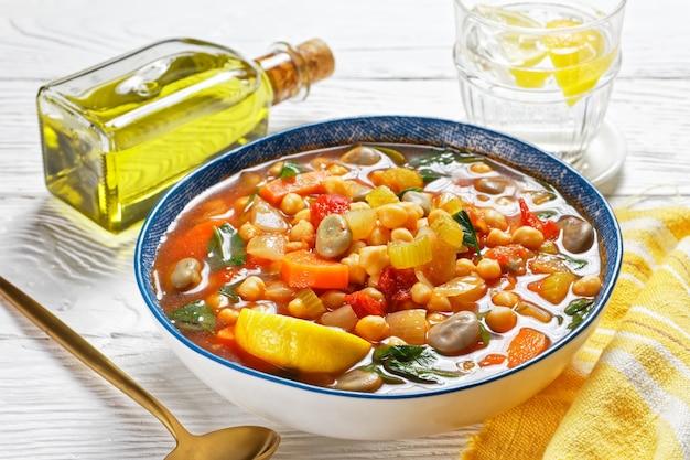 Марокканский суп из нута и зеленой фасоли в синей миске на белом деревянном столе, крупный план