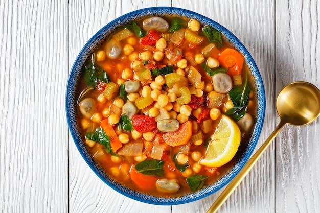 Марокканский суп из нута и зеленой фасоли в синей миске на белом деревянном столе, плоская планировка, макрос