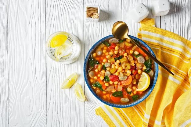 Марокканский суп из нута и зеленой фасоли в синей миске на белом деревянном столе, плоская планировка