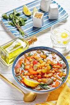 Марокканский суп из нута и зеленой фасоли в синей миске на белом деревянном столе, вертикальный вид