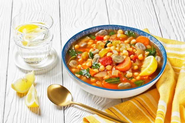 Марокканский суп из нута и зеленой фасоли в синей миске на белом деревянном столе