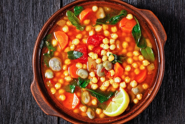 Марокканский суп из нута и зеленой фасоли в глиняной миске на деревенском деревянном столе, крупный план, плоская планировка