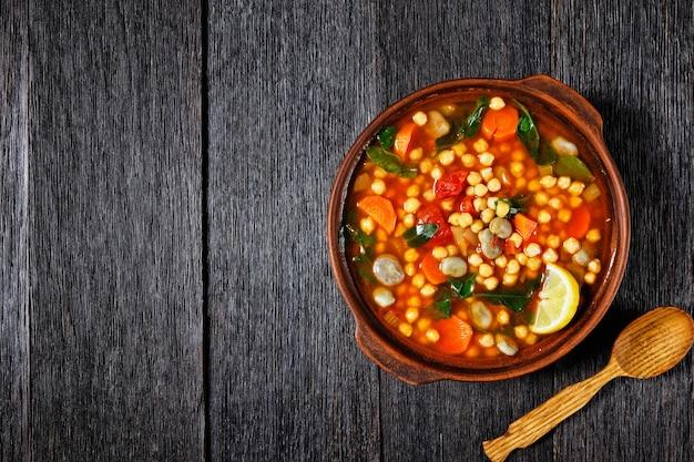 Марокканский суп из нута и зеленой фасоли в глиняной посуде на деревенском деревянном столе, плоская планировка, свободное место