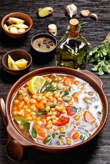 Марокканский суп из нута и зеленой фасоли в глиняной миске на деревенском деревянном столе