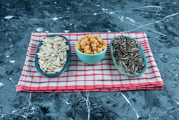 青いテーブルの上のティータオルのボウルにひよこ豆とヒマワリの種。