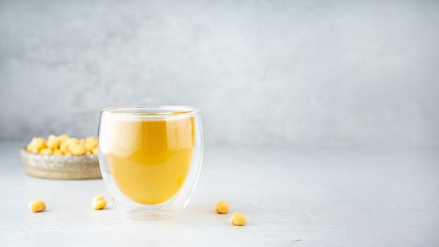 병아리콩 아쿠아파바. 계란 교체. 채식주의 요리 개념입니다. 유리 컵에 병아리콩 물과 세라믹 수제 접시에 병아리콩. 회색 배경에. 천연 친환경 제품. 공간을 복사합니다.