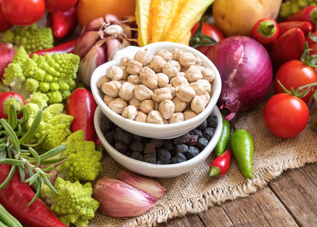 Chickpea in bowls with raw vegetables close up on a wooden table