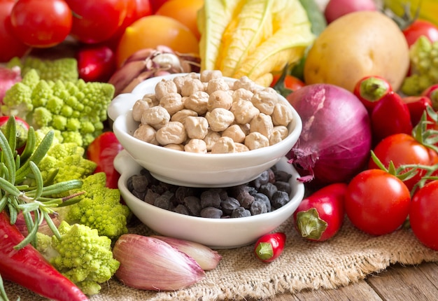 Chickpea in bowls with vegetables on a wooden table close up