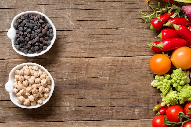 Chickpea in bowls with vegetables on a wooden table with copy space top view