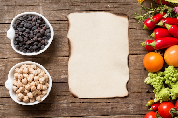 Chickpea in bowls with vegetables on a wooden table with paper copy space top view