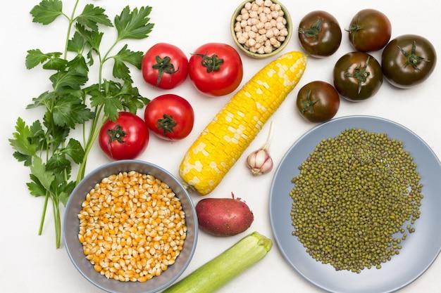 접시에 병아리콩, 옥수수, 녹두 곡물. 테이블에 노란 옥수수, 토마토, 파슬리 sprigs의 스윙. 흰색 배경. 플랫 레이