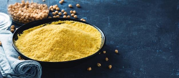暗いテーブルの上の黒いセラミックボウルにひよこ豆の粉