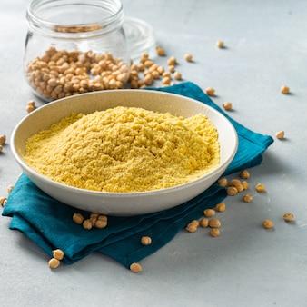 ライトテーブルの上の白いセラミックボウルにひよこ豆の粉