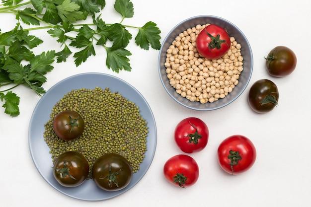회색 접시에 병아리콩 곡물과 녹두. 토마토와 테이블에 파 슬 리의 sprigs입니다. 흰색 배경. 플랫 레이