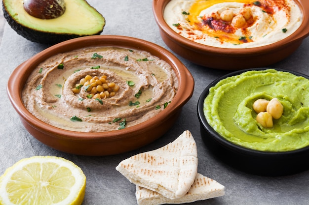 Chickpea hummus, avocado hummus and lentils hummus on gray stone