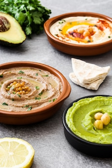 Chickpea hummus, avocado hummus and lentils hummus on gray stone