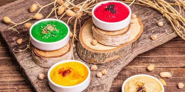 병아리콩 후무스 배경입니다. 다양한 야채와 향신료로 맛을 냅니다. 빈티지 나무 테이블, 현대 하드 라이트, 어두운 그림자, 배너