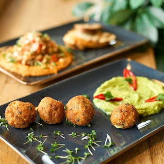 Chickpea hummus and guacamole and falafel dish on blue plate on a wooden table