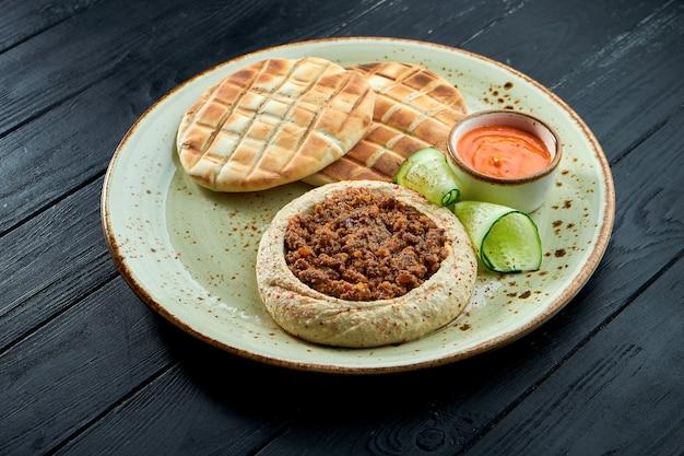 ひよこ豆のフムスにオリーブオイルとひき肉を添えて、ダークウッドの背景のプレートに焼きピタを添えて。