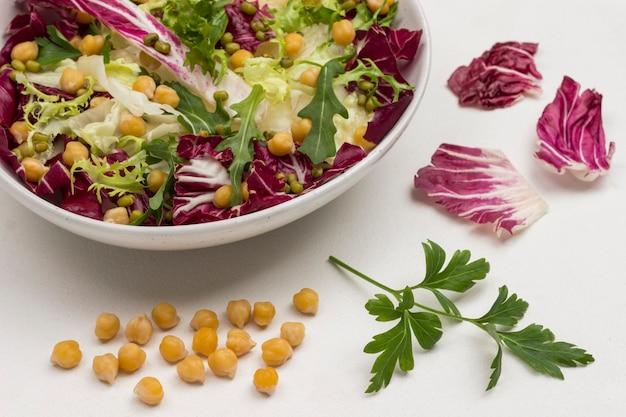 병아리 콩, 녹두, 검은 색 접시에 여러 가지 빛깔의 잎이 많은 채소 믹스. 비건 음식. 면역 강화를위한 자연 요법. 평면도. 확대.