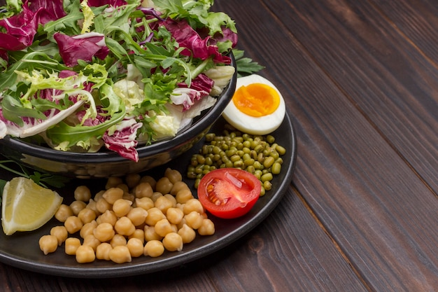 병아리 콩, 녹두, 검은 색 접시에 여러 가지 빛깔의 잎이 많은 채소 믹스. 비건 음식. 평면도. 확대. 공간 복사
