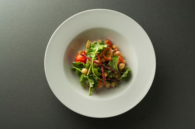 Chickpea salad with fresh vegetables - cucumbers, tomatoes, beetroot, spinach.