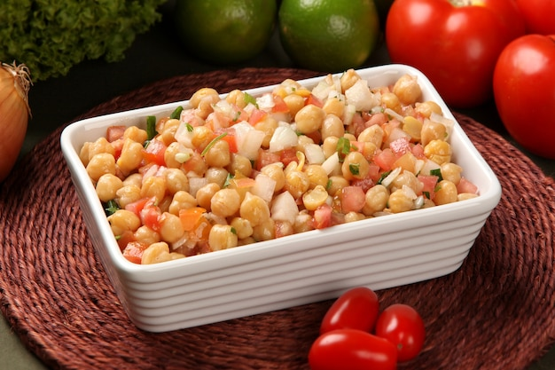 Chickpea salad, with some ingredients in the table.