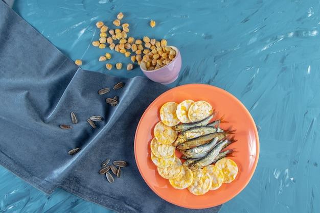 Нут, семена рядом с сушеной килькой и сырными чипсами в тарелке на полотенце, на синей поверхности.