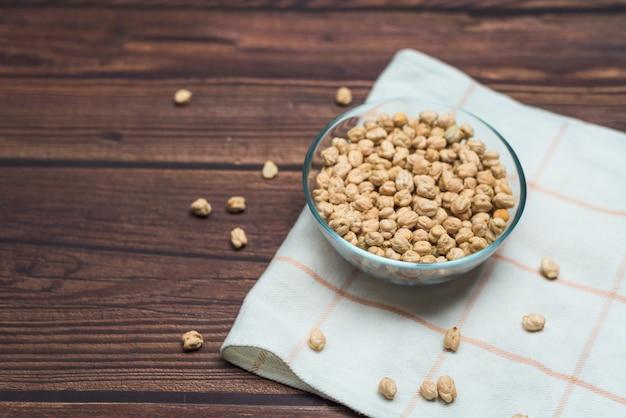 ヒヨコマメの種子。有機健康シリアル。木製のプレートで小麦粉