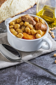 Блюдо из нута (тушеное по-мадридски). с говядиной, чоризо, беконом, морковью и оливковым маслом. средиземноморская диета. самодельный вид. с копией пространства.