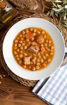 Chickpea stew dish with beef, sausage, bacon, carrots and olive oil