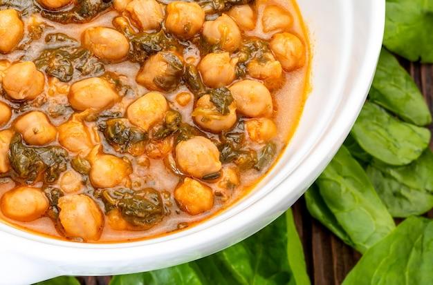 ほうれん草とひよこ豆のシチュー(ポタヘ)。秋と冬のおいしいスプーン料理。伝統的な食べ物。前景。