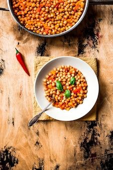 토마토, 노란색 후추, 칠리, 바질 잎을 곁들인 병아리 콩 스튜. 상위 뷰 사진, 나무 표면. 접시에 숟가락.