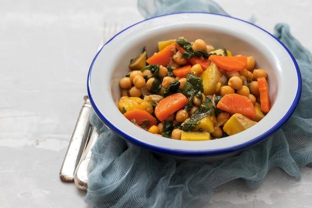 당근과 흰 그릇에 시금치와 병아리 콩